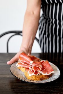 A waiter in a striped apron placing a plate of proscuitto on chargrilled bread on to the table