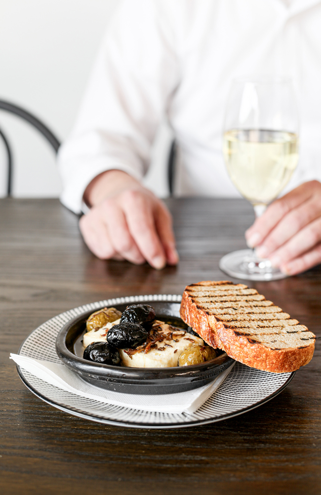 A plate of baked feta with marinated black olives and chargrilled bread on a table with a man holding a wine glass in the background