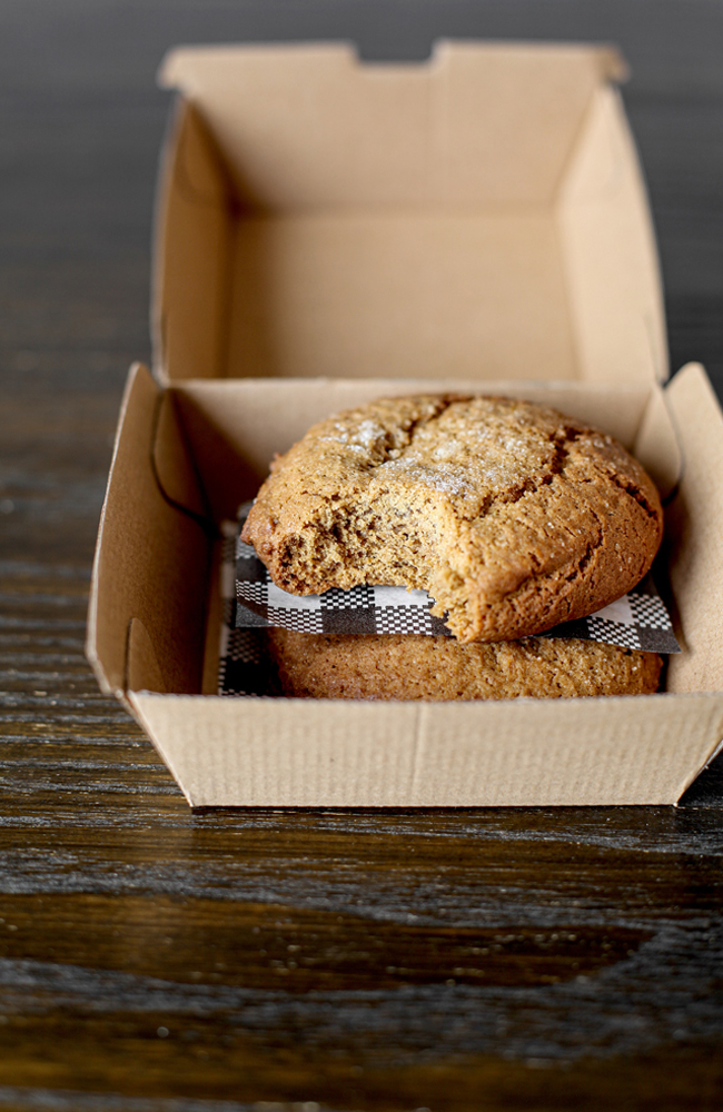 A biscuit or cookie in a cardboard takeaway container with a bite taken out of it