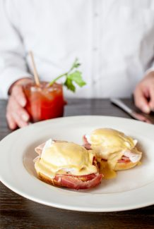 A white plate with poached eggs and ham topped with Hollandaise sauce. A man in a white shirt sits behind it with cutlery and a bloody mary in hand.